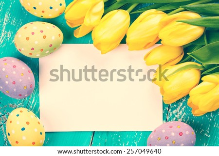 Colorful Easter eggs, tulips and blank card on blue wooden background - stock photo