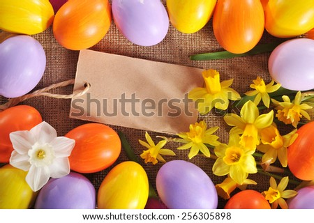 colorful easter eggs with narcissus on jute bag  - stock photo