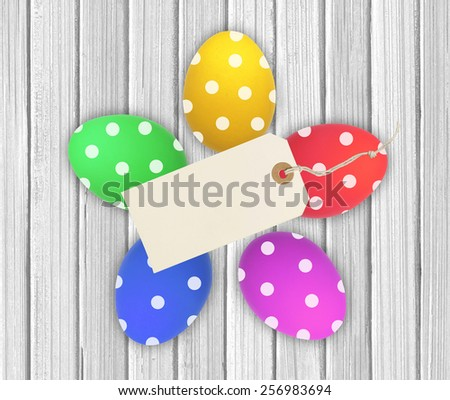 Colorful Easter Eggs with tag card over wooden background - stock photo