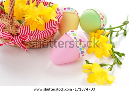Colorful easter eggs with yellow freesia flowers