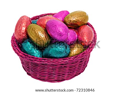 colorful easter eggs wrapped in shiny foil in wicker basket isolated on white background