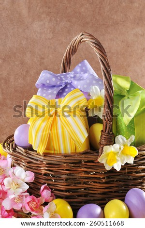 colorful easter presents with bow in easter basket with narcissus and painted easter eggs