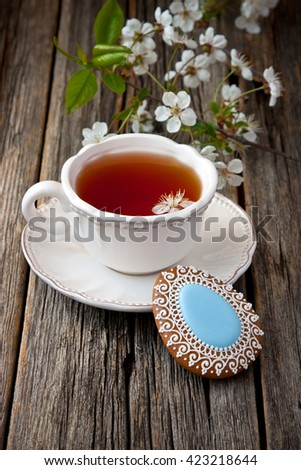 Colorful egg-shaped cookies for easter  and tea cup on  wooden  background