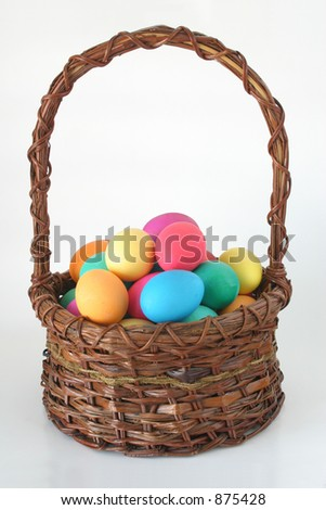 Colorful Eggs:  Colorful Easter eggs gathered in a brown wicker basket. - stock photo