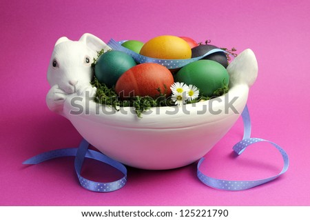 Colorful eggs in white bunny rabbit bowl with grass, white daisy and blue polka dot ribbon against a pink background. - stock photo