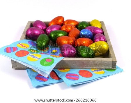 Colorful eggs of chocolate on blue easter napkins over white - stock photo