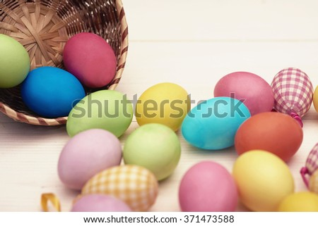 Colorful eggs scattering from a wicker bowl - stock photo