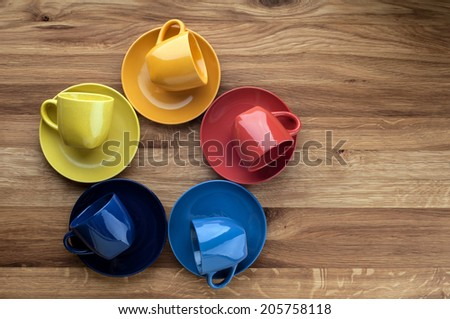 Colorful empty coffee cups on wooden background. - stock photo