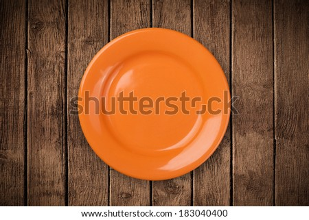 Colorful empty shiny plate on grungy background table  - stock photo