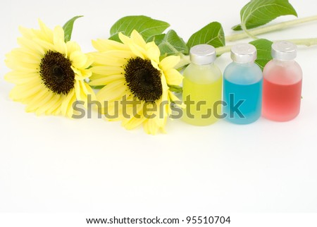 Colorful essential oil and sunflower on white background - stock photo