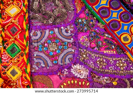 Colorful ethnic Rajasthan cushion cover and belts with mirrors on flea market in India - stock photo