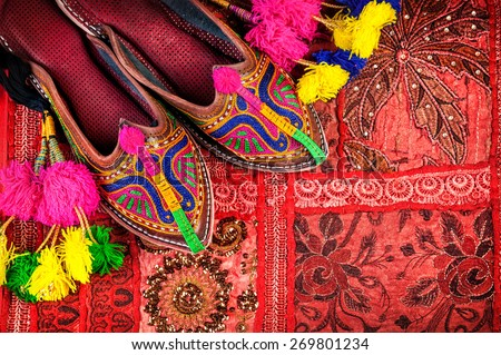 Colorful ethnic shoes and camel decorations on red Rajasthan cushion cover on flea market in India - stock photo