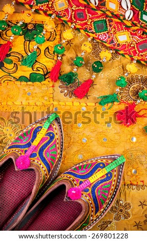 Colorful ethnic shoes and gipsy belt on yellow Rajasthan cushion cover on flea market in India - stock photo