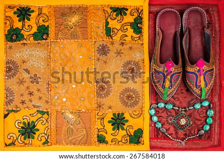 Colorful ethnic shoes, necklace and yellow Rajasthan cushion cover on flea market in India - stock photo