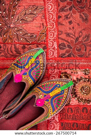 Colorful ethnic shoes on red Rajasthan cushion cover on flea market in India - stock photo