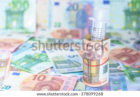 Colorful euro currency with syringe costs for the medical insurance,Focus on number 50 of currency roll and blurry background - stock photo