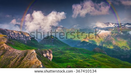 Colorful evening scene with a rainbow after huge rain. View from top of famous Grossglockner High Alpine Road. Austria, Alps. Europe.  - stock photo