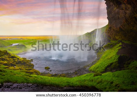 Colorful evening view from the middle of famous Seljalandfoss Waterfall. Braethtaken sunset in south Iceland, Europe. Artistic style post processed photo.