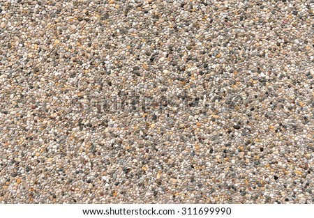 Colorful exposed aggregate concrete with gray, brown and yellowish pebbles on a facade  - stock photo