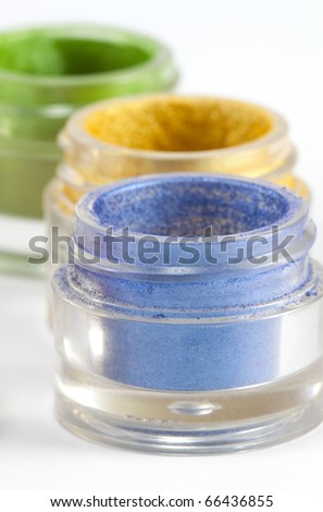 Colorful eye shadow jars on white background. - stock photo
