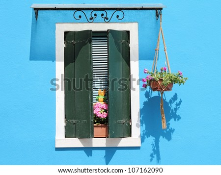 colorful facade with window with shutters, typical vivid colors for village Burano on venetian lagoon, Italy, Europe - stock photo