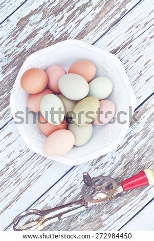 Colorful farm fresh chicken eggs from free range chickens with an antique egg beater over a rustic wooden background. - stock photo