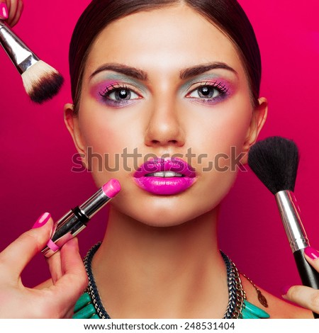 Colorful fashion beauty portrait of young woman with  bright make up , big pink  full lips and effect necklace .Beautiful young female getting her make-up done against color background. - stock photo