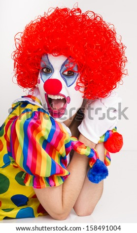 Colorful female circus clown actress speaking out excited performing - stock photo