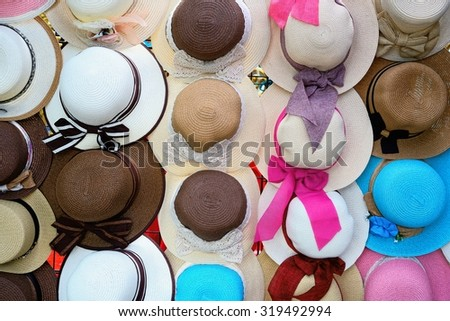 Colorful female summer hats lie on the local street market / Colorful female summer hats  - stock photo