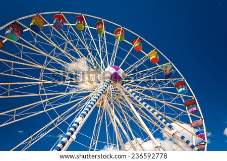 Colorful ferris wheel against a blue sky background.