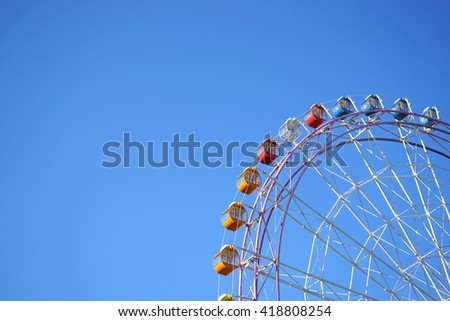 Colorful Ferris wheel in a sunny blue sky - stock photo