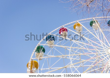 Colorful Ferris wheel in the park on a blue sky background