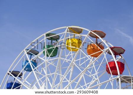 Colorful ferris wheel over blue sky - stock photo