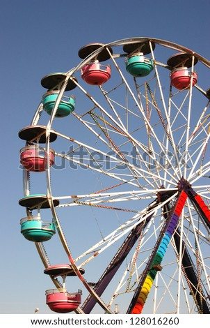 Colorful Ferris wheel spins against a clear blue sky. - stock photo