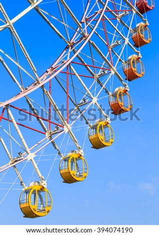 Colorful ferris wheel with vivid baskets on blue sky background (nobody) - stock photo