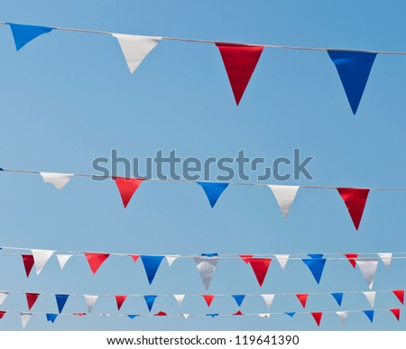 colorful festive bunting flags against a blue sky background (United Kingdom) - stock photo