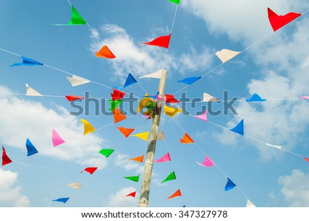 colorful festive bunting flags against, on blue and clouds sky in Thailand - stock photo
