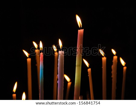 Colorful festive candles on dark background. Sunlight filtered through the stained glass window reflected on the candles. - stock photo