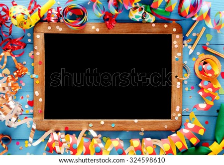Colorful festive frame with multicolored coiled party streamers on a blue wooden background around a vintage slate with a clean chalkboard and copyspace - stock photo