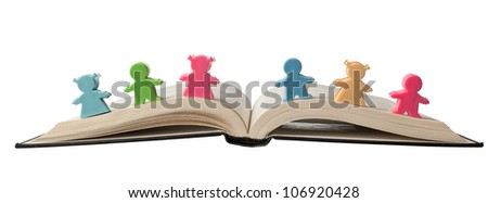 Colorful figurines on top of an open book isolated on white background - stock photo