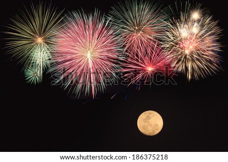 Colorful fireworks and full moon  over black background - stock photo