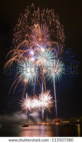 colorful fireworks display over the river - stock photo