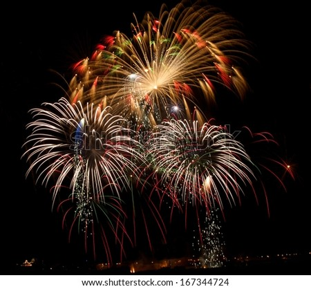 Colorful fireworks explosion in dark sky background, 4 of July, Independence day, explode, fireworks festival fragment close up with village silhouette in background in Malta,Malta fireworks festival - stock photo