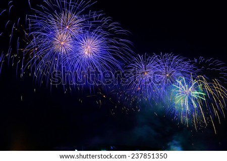 Colorful fireworks. Fireworks are a class of explosive pyrotechnic devices used for entertainment purposes. Visible noise due to low light, soft focus, shallow DOF, slight motion blur - stock photo