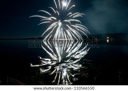 Colorful fireworks & moon reflecting off a calm lake - stock photo