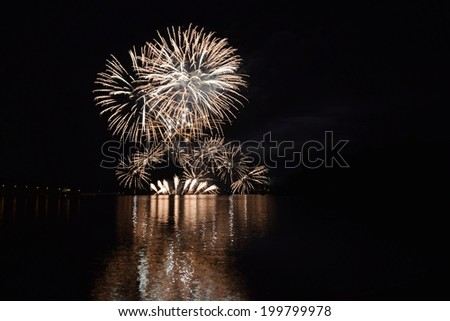 Colorful fireworks reflect from water - stock photo