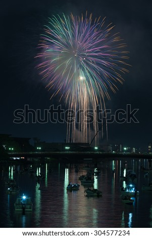 Colorful fireworks reflected in a river with many small boats and a cityscape along the side in the countryside of Kochi, Japan.