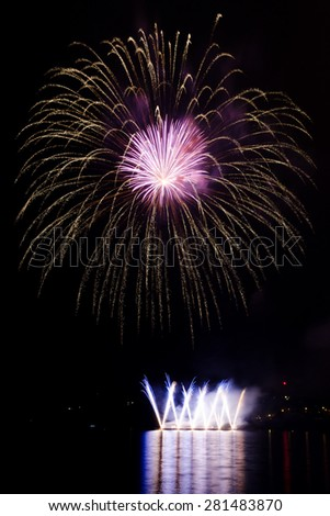 Colorful fireworks show above the lake - stock photo