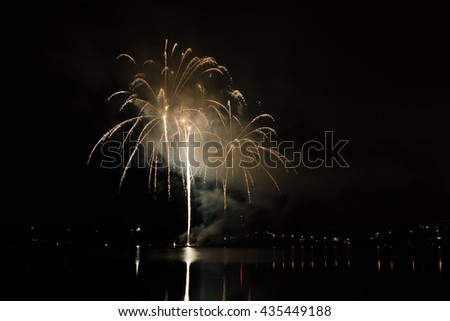 Colorful fireworks show with rockets bursting above the lake - stock photo