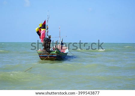 Colorful fisherman boat in lake with lighting in the morning on blue sky background:Close up,select focus with shallow depth of field:ideal use for background.